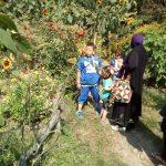 Foto: Ein Garten, links Sonnenblumen und Tomaten, rechts eine Frau mit Kopftuch und drei Kinder