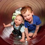 Foto: zwei Kinder nebeneinander kniend und lachend in einem roten Rohr