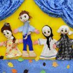 Foto: vier Puppen auf einer Bühne mit blauen Vorhängen und Boden, davon ein großer Mann und drei Frauen