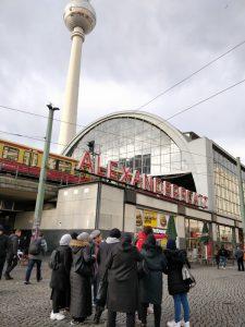 Foto: Brücke mit Zug, davor Schriftzug Alexanderplatz, unten steht eine Gruppe Frauen