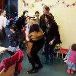 Foto: Erwachsene und Kinder Tanzen links im Bild, rechts spielen zwei Kleinkinder