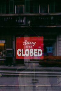 Foto: Ladentür, darin hängt ein rotes Schild auf dem Sorry we are closed steht
