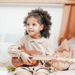 Foto: ein Mädchen frontal sitzt auf einem Bett und spielt auf einer Ukulele