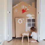 Foto: Kind vor Schrank, in den ein Papphaus steht. Kind malt Papphaus weiß an.