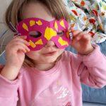 Foto: Kind mit rose Pullover hält sich eine selbstgebastelte rosa-gelbe Maske vors Gesicht