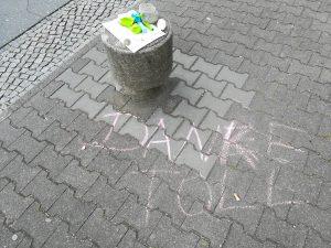 """Foto: Poller auf der Straße, mit Ballons und Pustefix drauf, davor geschrieben mit Kreide """"Danke Toll"""""""