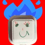 Foto: Pappkarton mit Gesicht vor rotem Hintergrund mit blauen Flammenhaaren
