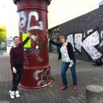 Foto: zwei Frauen lehnen sich an eine rote Litfaßsäule in der Mitte des Bildes