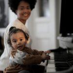 Foto: rechts ein Klavier, links ein Kleinkind, dass darauf spielt, im Hintergrund lächelt eine Frau in die Kamera
