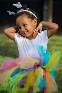 Foto: drei Jahre altes Mädchen im bunten Feen-Kostüm hebt beide Arme über den Kopf und lächelt zur Seite