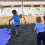 Foto: zwei Kinder von hinten, die eine Wiese entlanggehen. Beide halten große Hula-Hoop-Reifen.