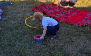 Foto: Kind von hinten auf Wiese, das zwei kleine Ringe und einen großen gelben Reifen aufhebt.