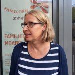Foto: Portrait von Frau mit Brille, blonden Haaren und blau-weiß gestreiften Hemd, die leicht nach links schaut