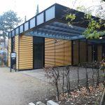 Foto: Ein gelber Pavillion frontal mit großer Glasfront rechts