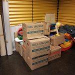 Foto: Umzugskisten und verpacktes Spielzeug vor einer gelben Wand