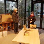 Foto: Raum mit großen Glasfenstern, im Hintergrund ein Regal, vorne ein Holztisch, dahinter stehen ein Mann und eine Frau mit Maske