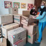 Foto: Viele gestapelte braune Umzugskartons, lins daneben zwei Fraun mit Maske
