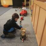 Foto: kind hockt links im Bild und spielt mit Holzautos, rechts im Bild.