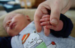 Foto: Neugeborenes Baby liegt und hält die Hand einer erwachsenen Person.