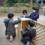 Foto: drei Kinder stehen und Knien vor einer Holzkonstruktion an der ein Erwachsener schraubt