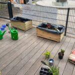 Foto: Eine Holzveranda, hinten zwei Blumenkästen, vorne Gartenhilfsmittel und frische Pflänzchen