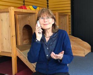 Foto: Eine mittelalte Frau mit Brille und lächelnd als Portrait mit einem Telefon am rechten Ohr