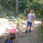 Foto: vorne links ein Mädchen mit Gießkanne, hinten rechts ein lachender junge mit Seifenblasen