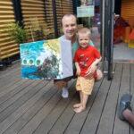 Foto: draußen, ein Mann hockend mit Junge stehend rechts von ihm. Der Mann hält bemalten Pappkarton in der Hand