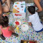 Foto: Vogelperspektive, ein Karton drum herum drei Kinder, die ihn bemalen
