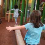 Foto: Innenraum mit einem Holzstamm auf dem zwei Mädchen balancieren